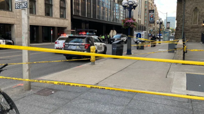 Police tape and vehicles line an intersection