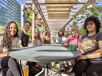 7 people sit around a table smiling