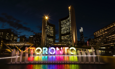 Multi-couloured Toronto sign at night with a water fountain in front of it