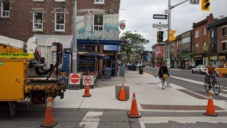 Photo of Bloor St at Brunswick Ave. In the foreground, an Electrical vehicle is parked and there are pylons surrounding it on the road and sidewalk. There are new signs on the sidewalk to be installed on the street for the planned contra-flow bike lanes o