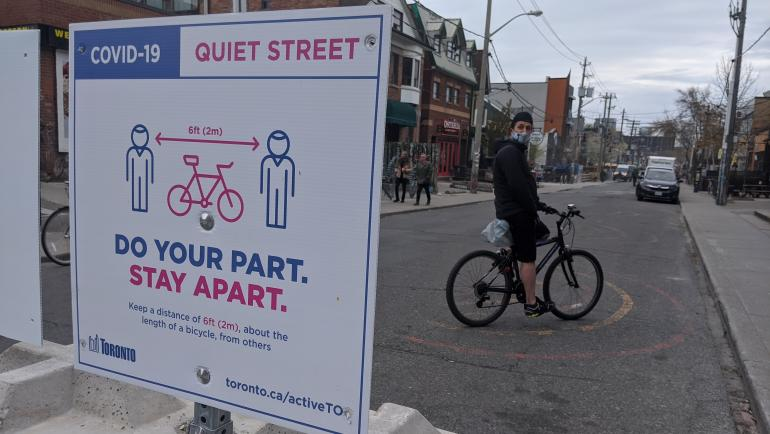 """Person with a mask on a bike beside a sign that reads """"Covid-19 Quite Street. Do your part. Stay Apart."""