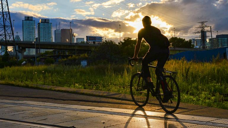 A person rides a bike over streetcar tracks in an industrial area. The setting sun outlines them leaving their shape a shadow in the foreground.