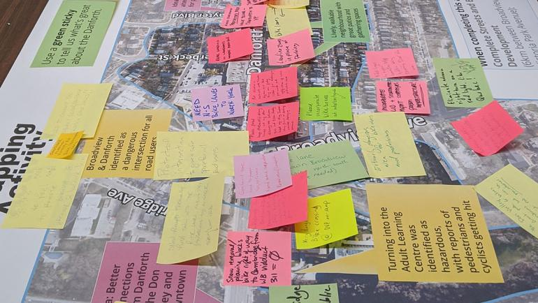 Multi-coloured sticky notes with comments are placed on large maps of Danforth Ave