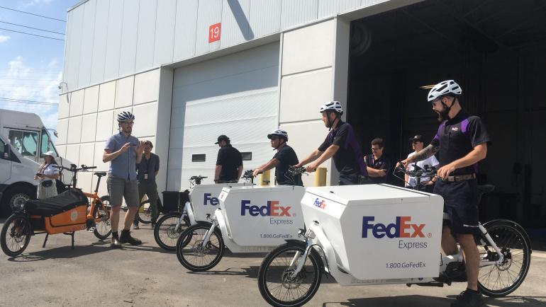 Several FedEx cargo bikes with riders are lined up next to a Cycle Toronto cargo bike. A person in plain clothes gives instructions