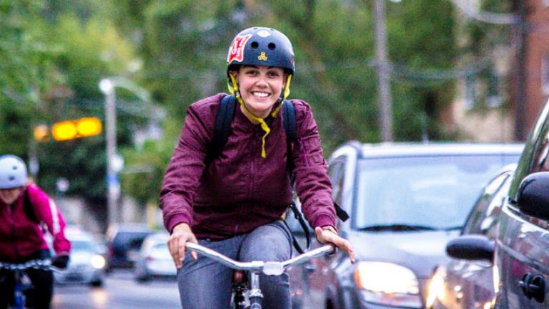 A woman smiles as she rides her bicycle in the foreground of the photo