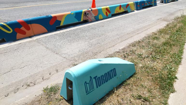 Colourfully painted low concrete walls. One has the Toronto City logo on it in blue.