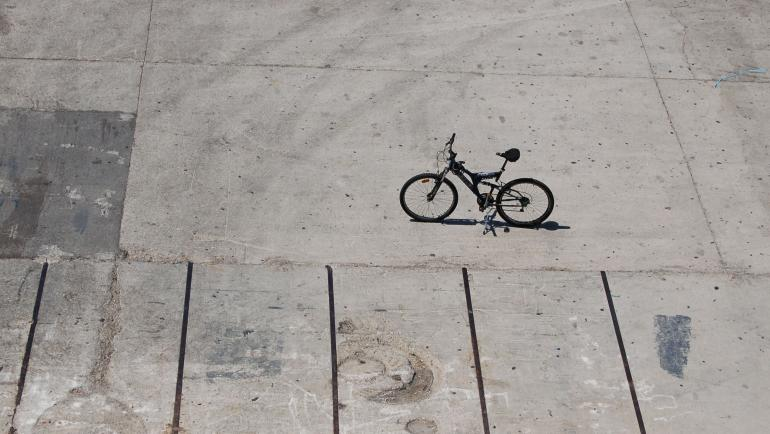 one lonely bike parked in parking lot