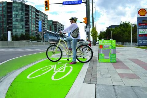 A person waits, sitting on their bicycle, to cycle through an intersection. They wait in a section of the road that has a bright green bike box painted, a location intended to be used to make a left-hand turn on a bicycle.