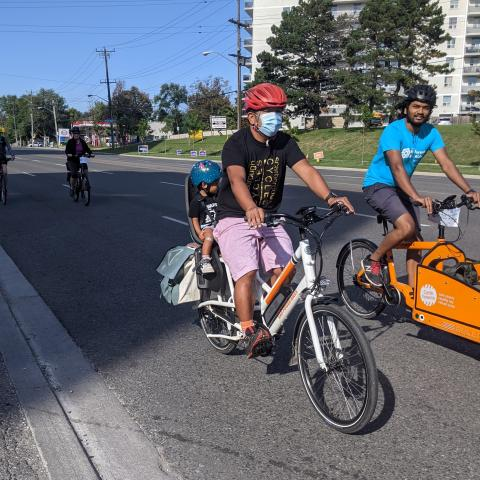 A man with a mask rides a bike with his child on the the back.
