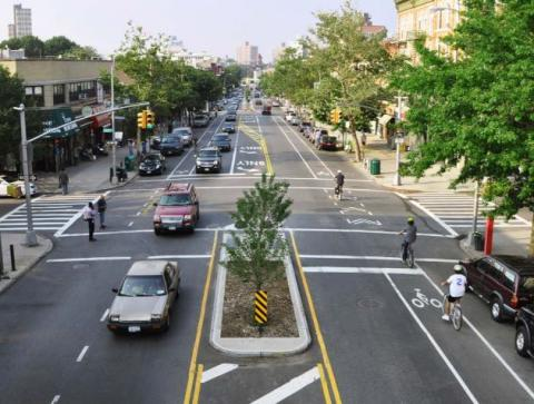 The image shows a street, from left to right, with parking, a bike lane, a travel lane, a turn pocket and planting zone to form the median, a travel lane in the opposite direction, a bike lane, and parking.