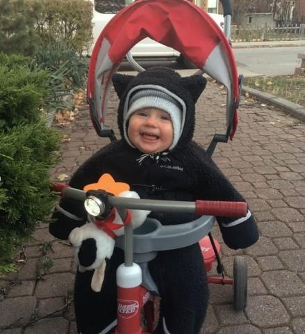 Violet Perry sits, smiling in a tricycle. She is bundled up for winter and has a black snowsuit and hat on.
