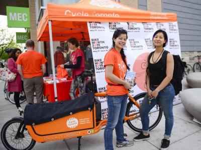Two people stand in front of a orange Cycle Toronto tent smiling.