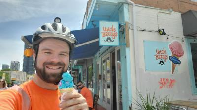 A man stands holding an ice cream cone in front of the store Uncle Betty's