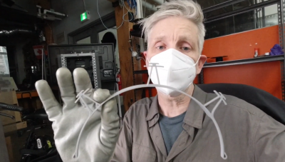 Tim Willison wears a facemask and gloves while he shows off a plastic semi-circle with attachment points