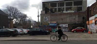 Michaela pedalling along Cecil Street with the CN Tower in the background