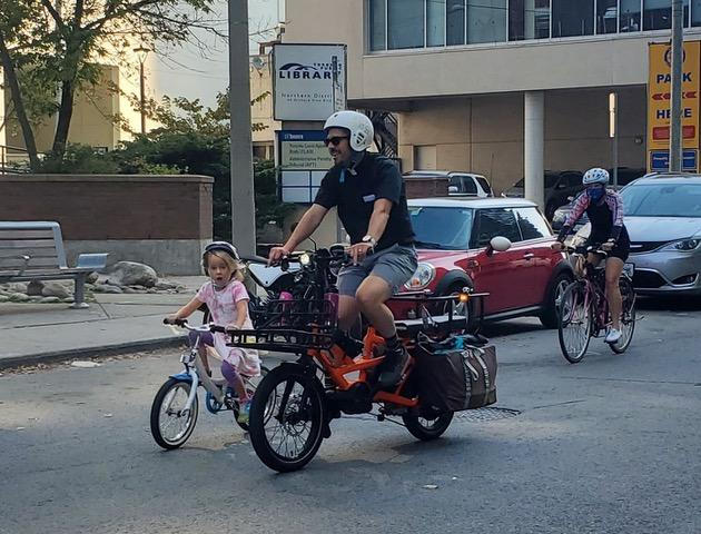 A man rides a packed cargo bike next to a very young person that is also riding a bike.