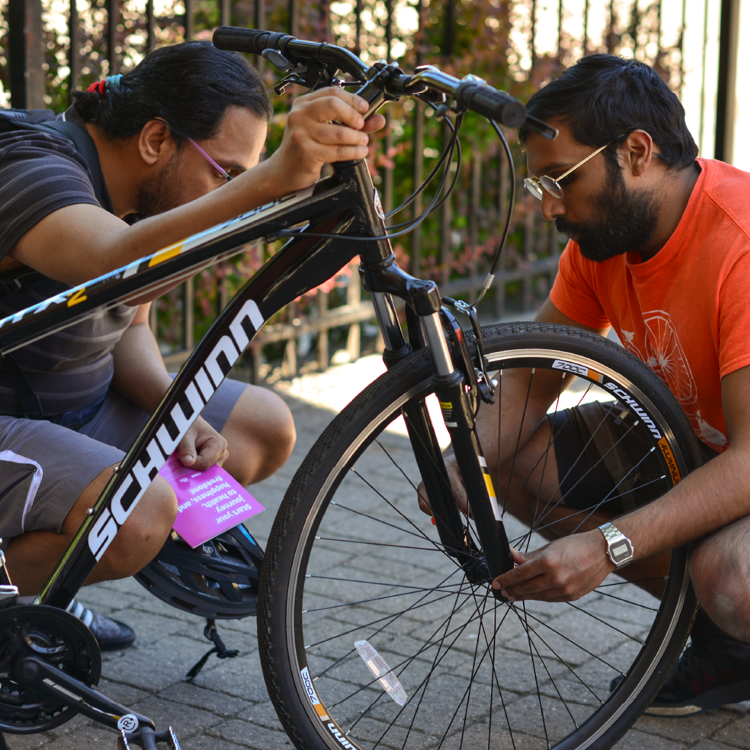 Two people examine a bike.