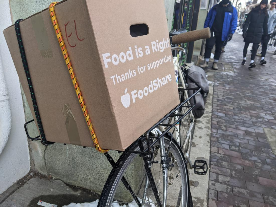 """A box on the back of a bike says """"Food is a right, thanks for supporting Foodshare"""""""