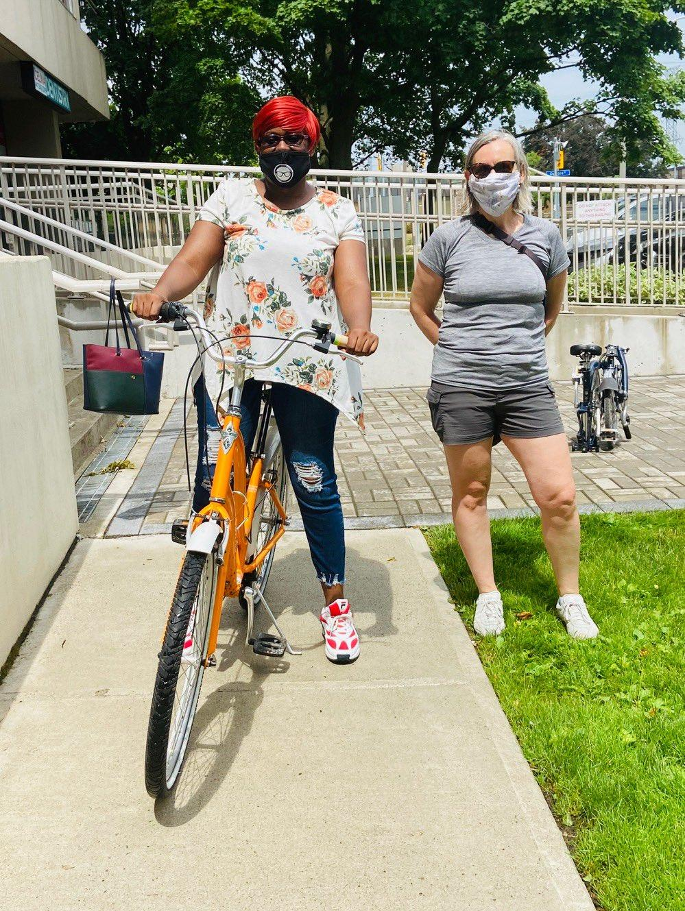 Two women with masks on pose. The woman on the left stands over a new looking orange bike.
