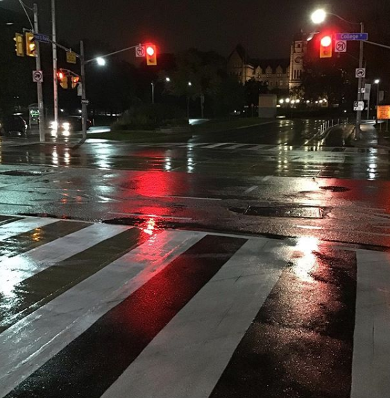 Wet roads reflect street lights at night.
