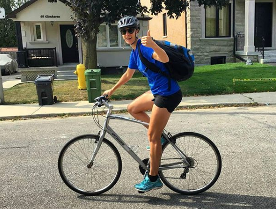 A person on a bike in a blue shirt smiles broadly and gives a thumbs up