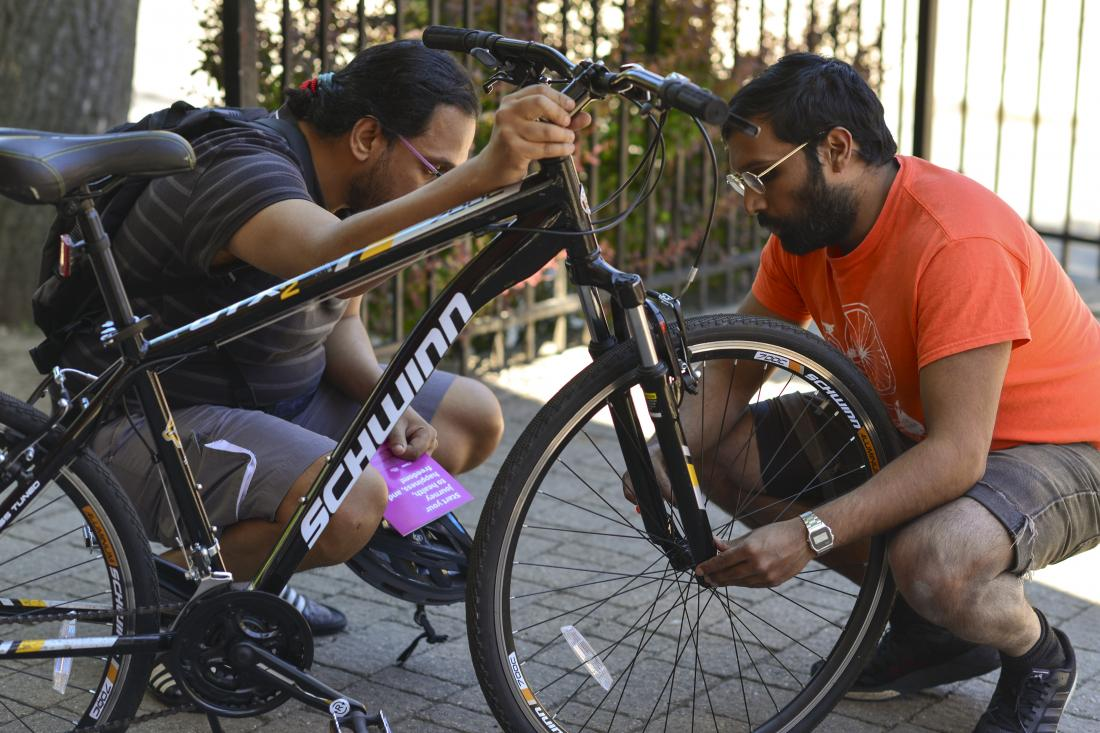 Cycling educator instructs adult student on how to check their quick release