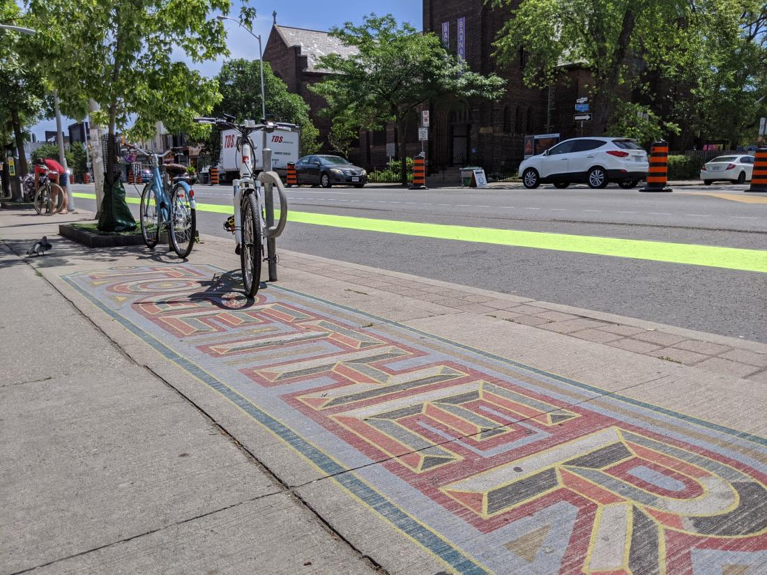 "A swath of green paint runs through a road. Parked bikes line the street. A sidewalk mural reads ""Together"""