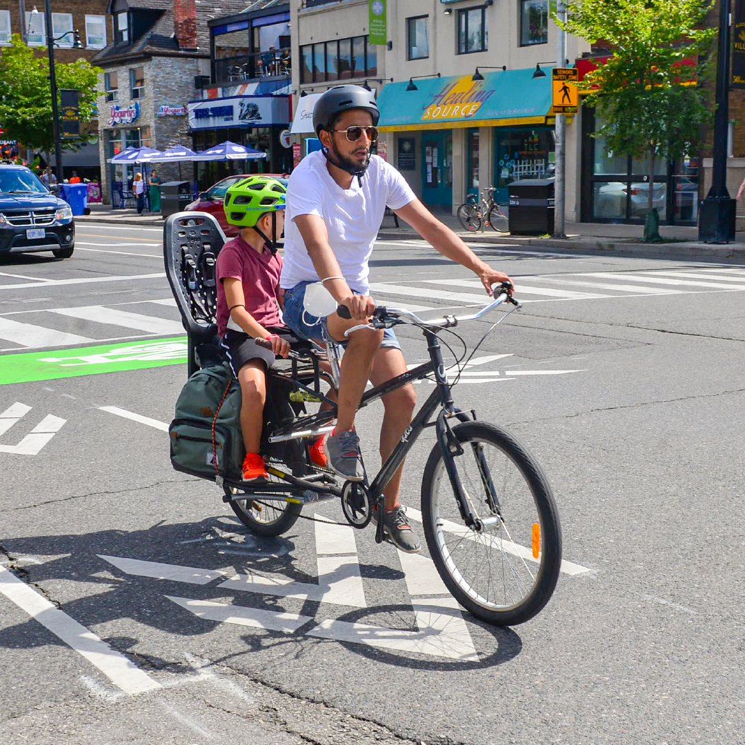 A person rides a bike with a child in a child seat.