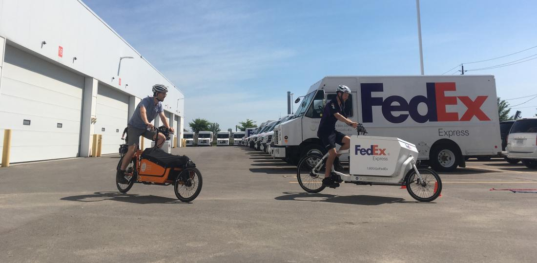 Cycle Toronto and FedEx ride cargo bikes in a van filled parking lot