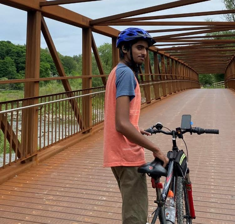 Man poses with his bike on a bridge