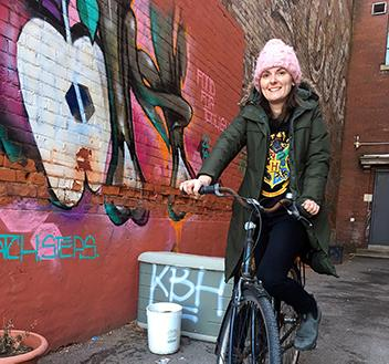 Theresa on her bike with mural in the background