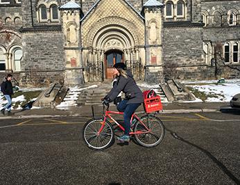Léa riding her bike on King's College Circle at U of T