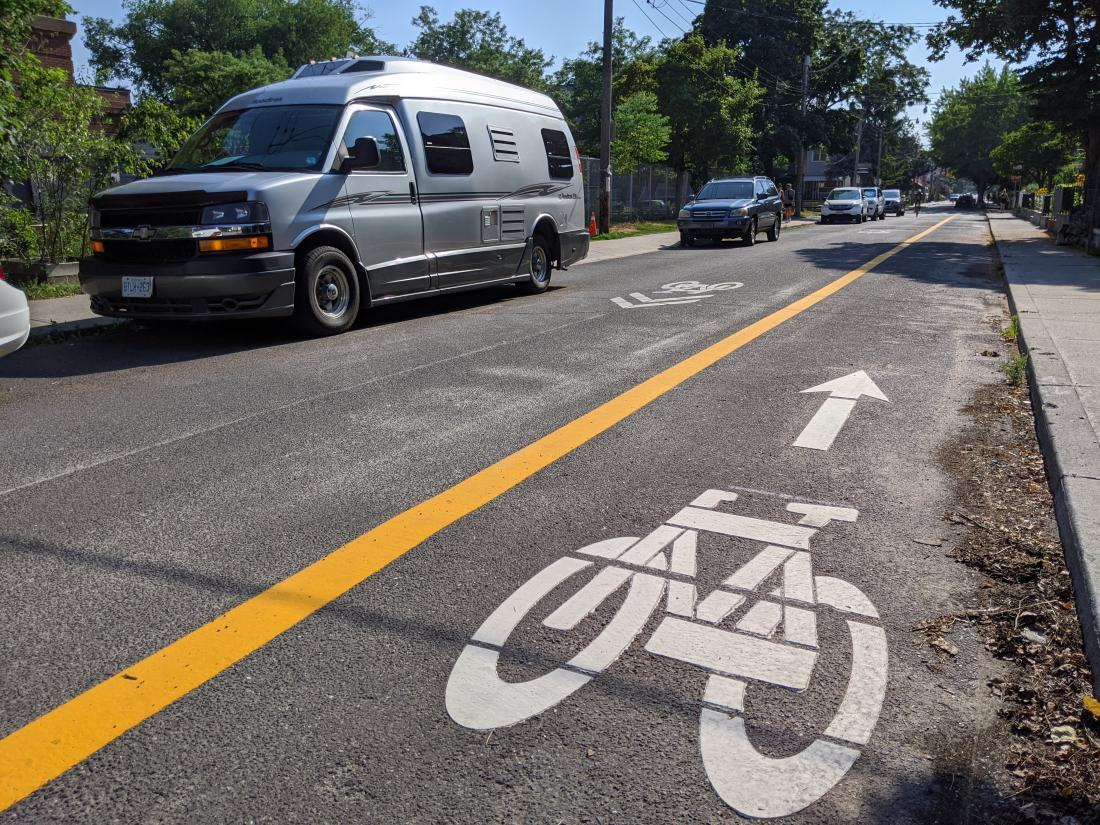A bike symbol with an arrow is on the right side of the road. A yellow line separates it from oncoming traffic