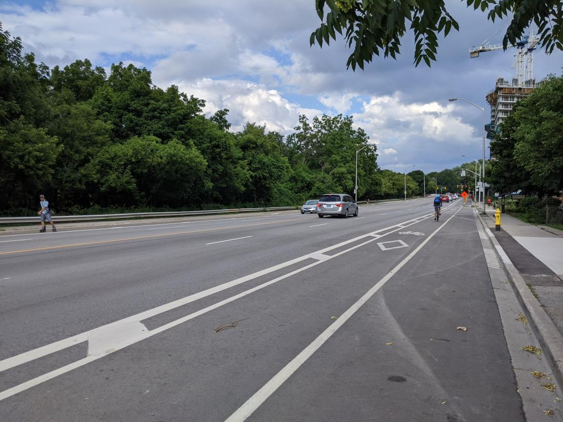 A painted bike lane has parking on the right and driving on the left.