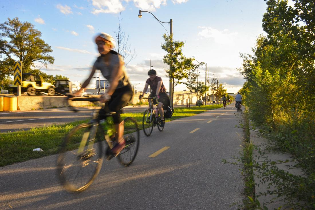 At sunset people ride on a paved path that is separate from traffic.