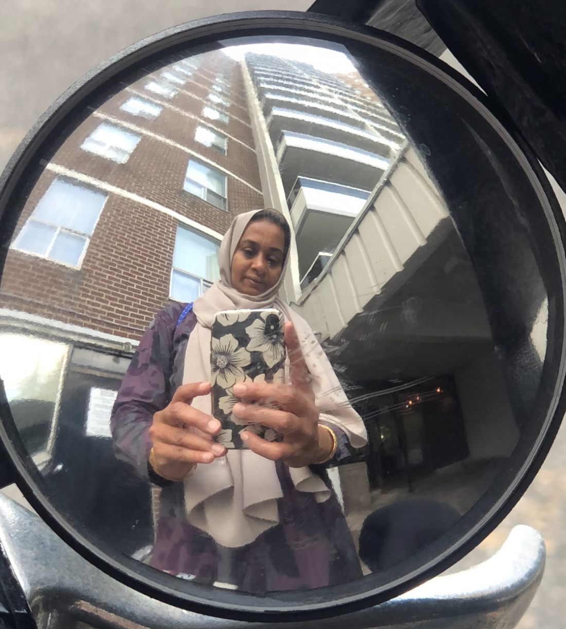 Woman takes a picture of herself in her bikes mirror