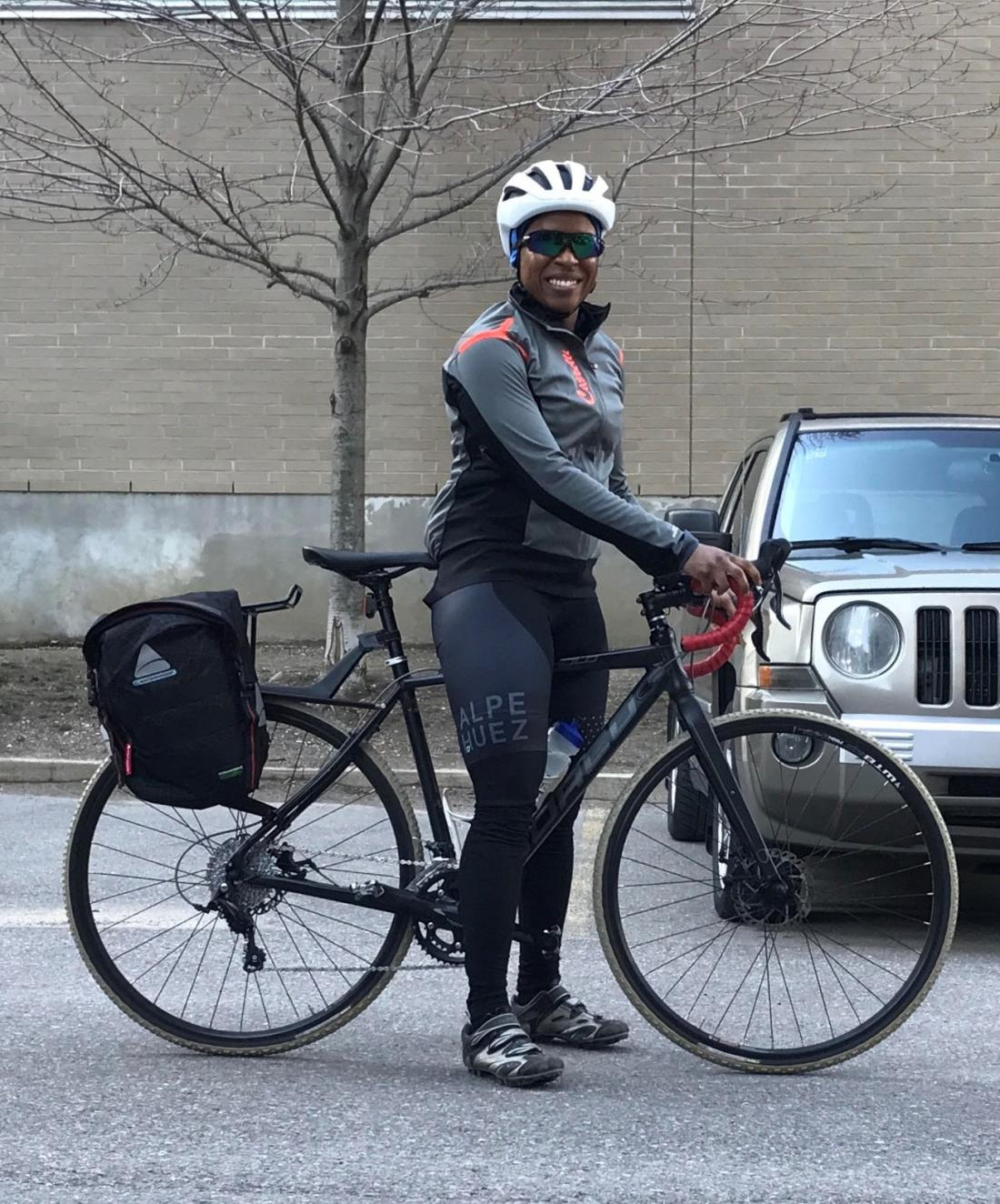 Woman poses with a bike and panniers