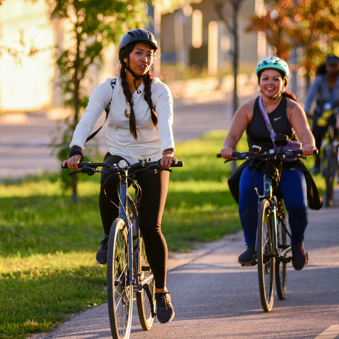 People ride bikes on a path while talking