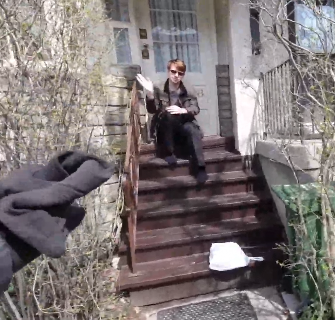 Person sits on porch with bag on steps