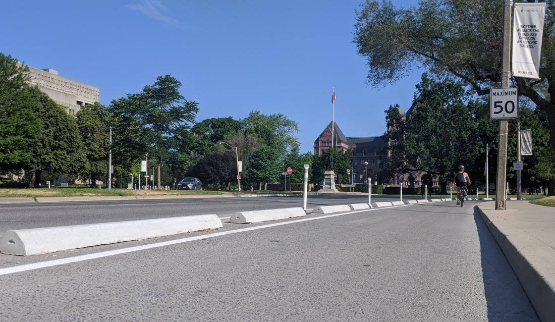 Concrete curbs and bollards separate a bike lane from a wide boulevard. A magnificent building is in the background