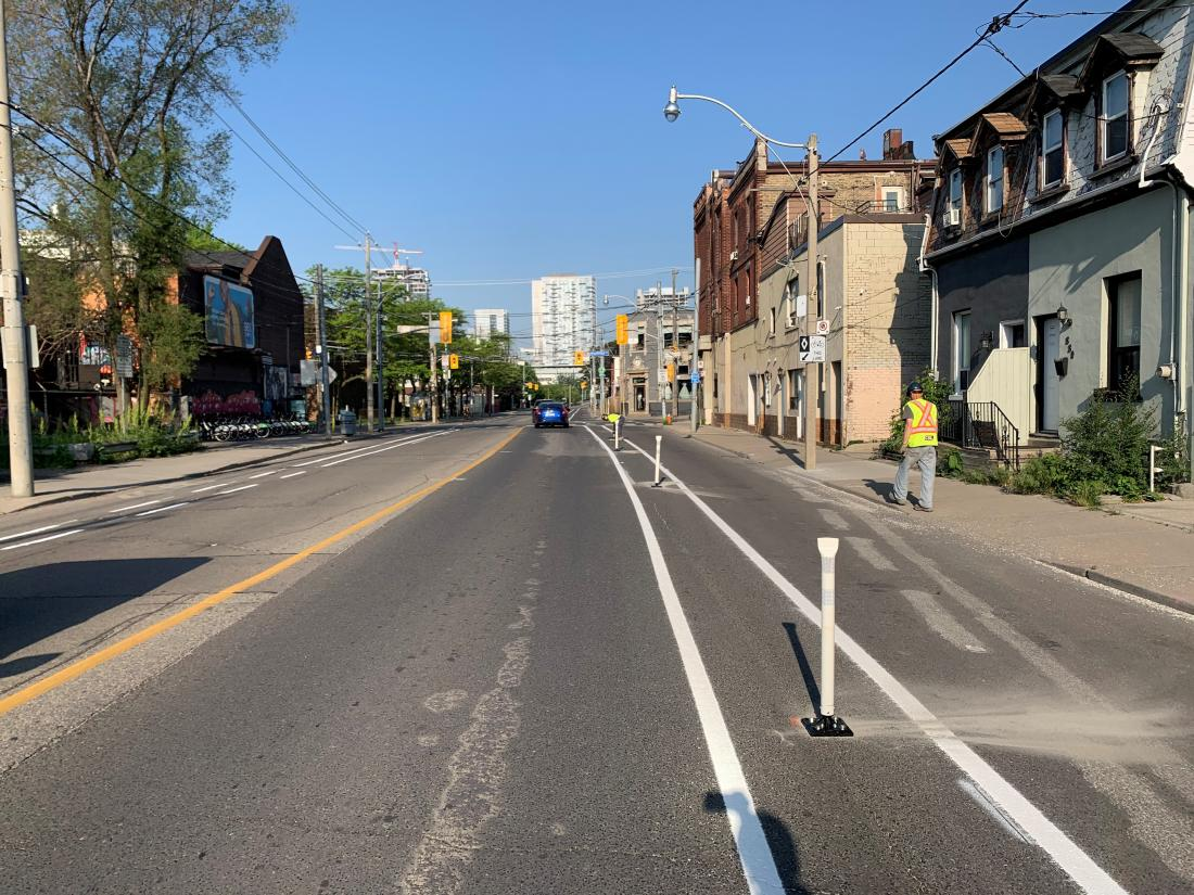 Streetcar tracks run down the middle of a street. The outside lanes have bollard separated bike lanes